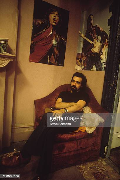 Martin Scorsese sitting beneath posters of rock icons Mick Jagger and Jimi Hendrix on the set of Taxi Driver