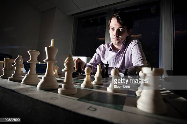 Martin Shkreli chief investment officer of MSMB Capital Management sits for a photograph behind a chess board in New York US on Wednesday Aug 10 2011...