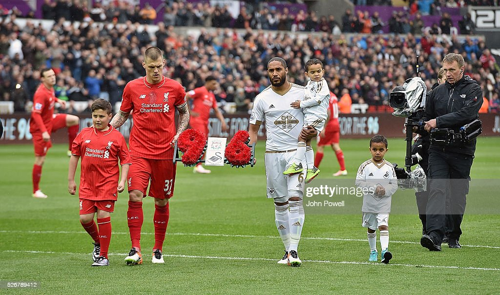 <a gi-track='captionPersonalityLinkClicked' href=/galleries/search?phrase=Martin+Skrtel&family=editorial&specificpeople=5554576 ng-click='$event.stopPropagation()'>Martin Skrtel</a> of Liverpool and <a gi-track='captionPersonalityLinkClicked' href=/galleries/search?phrase=Ashley+Williams+-+Futebolista&family=editorial&specificpeople=13495389 ng-click='$event.stopPropagation()'>Ashley Williams</a> of Swansea City carry a wreath to Barry Devonside, father of Hillsborough victim Christopher Devonside as the teams remember the 96 victims of the Hillsborough disaster during a Premier League match between Swansea City and Liverpool at the Liberty Stadium on May 01, 2016 in Swansea, Wales.