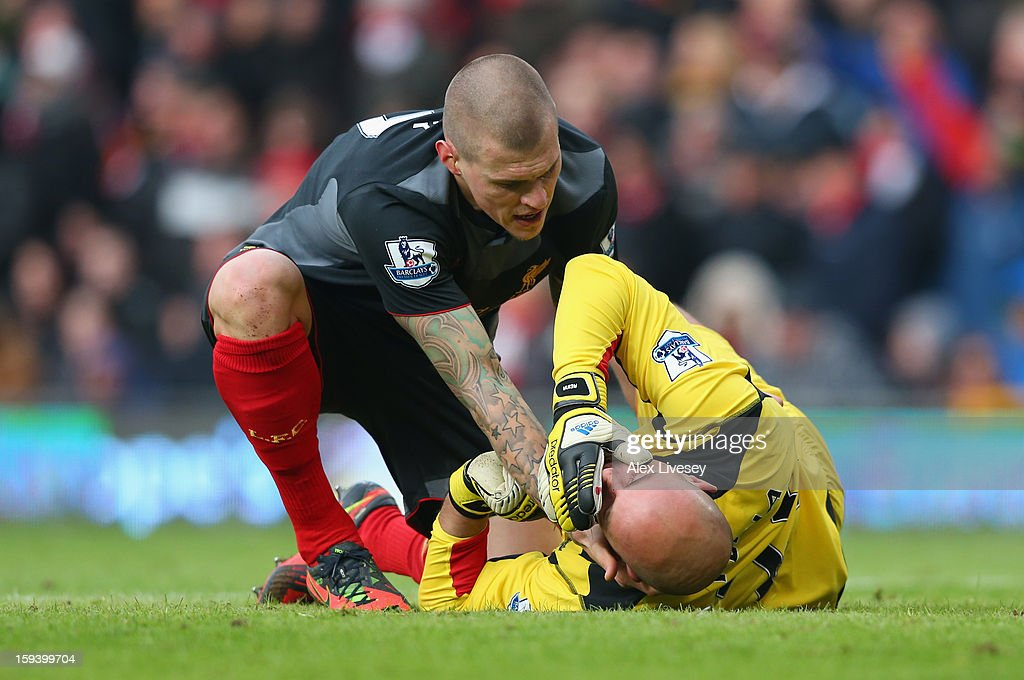 Martin Skrtel of Liverpool tends to team-mate Pepe Reina as he lies injured during the Barclays Premier League match between Manchester United and Liverpool at Old Trafford on January 13, 2013 in Manchester, England.
