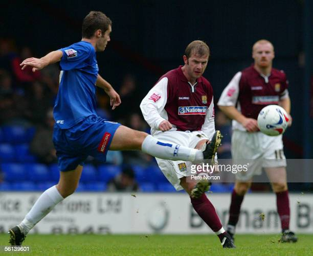 Martin Smith of Northampton Town beats Keith Briggs of Stockport County during the Coca Cola League Two match between Stockport County and...