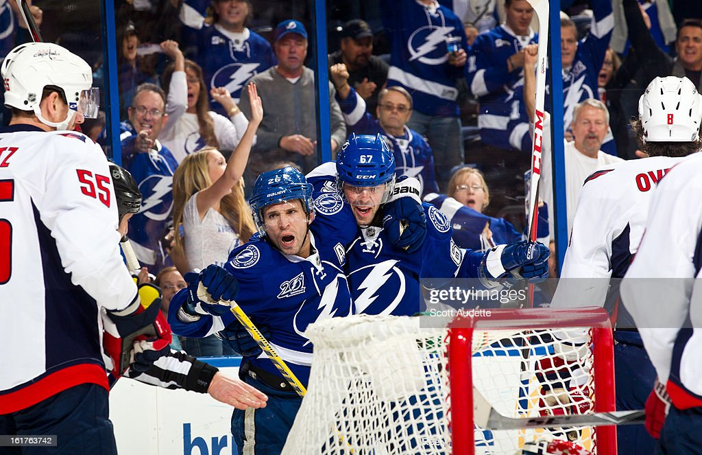 Martin St. Louis #26 and Benoit Pouliot #67 of the Tampa Bay Lightning celebrate after a goal during the first period of the game against the Washington Capitals at the Tampa Bay Times Forum on February 14, 2013 in Tampa, Florida.