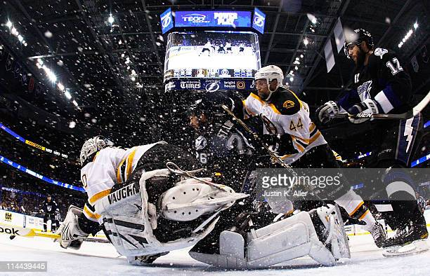 Martin St Louis and Simon Gagne of the Tampa Bay Lightning vie for position with Tim Thomas and Dennis Seidenberg of the Boston Bruins in Game Three...