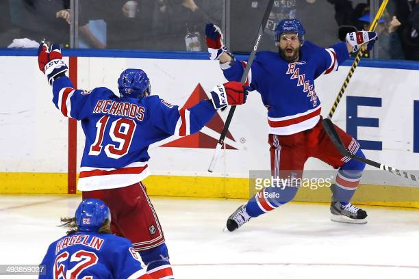 Martin St Louis of the New York Rangers celebrates with teammates Brad Richards after scoring the game winning shot in overtime against Dustin...