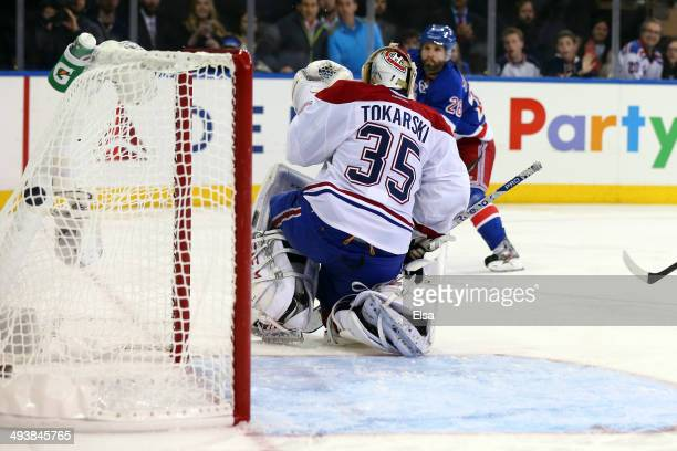 Martin St Louis of the New York Rangers scores the game winning shot in overtime against Dustin Tokarski of the Montreal Canadiens to win Game Four...