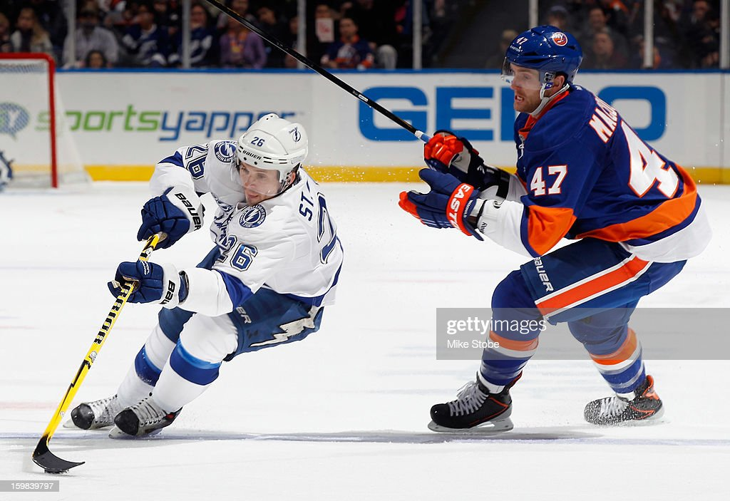 Martin St. Louis #26 of the Tampa Bay Lightning controls the puck in front of Andrew MacDonald #47 of the New York Islanders at Nassau Veterans Memorial Coliseum on January 21, 2013 in Uniondale, New York.