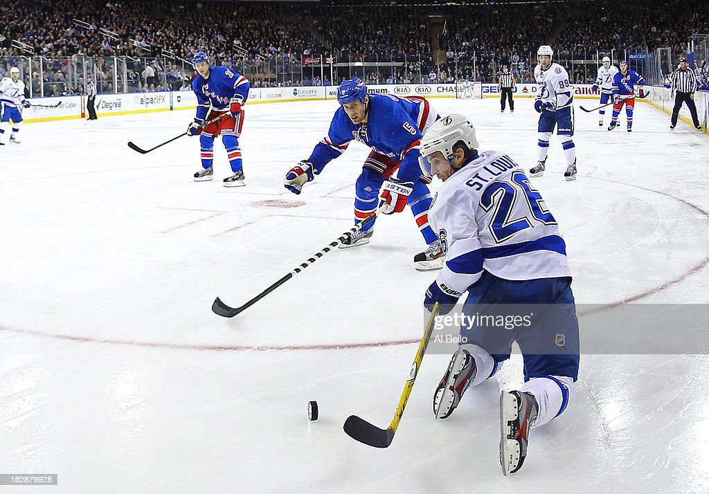 <a gi-track='captionPersonalityLinkClicked' href=/galleries/search?phrase=Martin+St.+Louis&family=editorial&specificpeople=202067 ng-click='$event.stopPropagation()'>Martin St. Louis</a> #26 of the Tampa Bay Lightning dives for the puck as Dan Girardi #5 of the New York Rangers chases during their game at Madison Square Garden on February 28, 2013 in New York City.