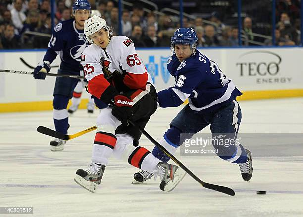 Martin St Louis of the Tampa Bay Lightning hits Erik Karlsson of the Ottawa Senators at the Tampa Bay Times Forum on March 6 2012 in Tampa Florida