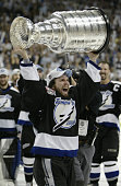 Martin St Louis of the Tampa Bay Lightning holds the Stanley Cup above his head after the victory over the Calgary Flames in Game seven of the NHL...