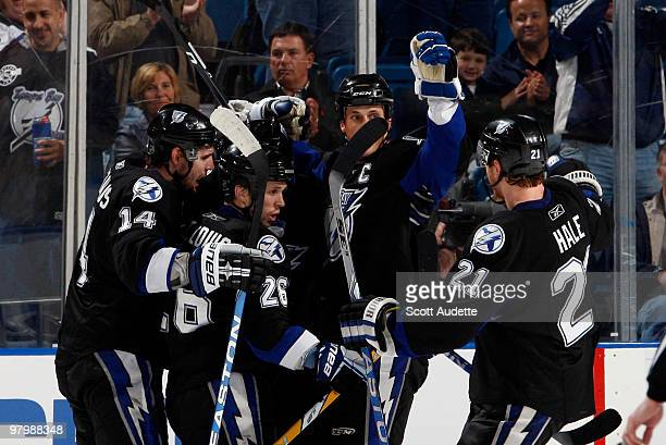 Martin St Louis of the Tampa Bay Lightning is congratulated on his goal against the Carolina Hurricanes by teammates Andrej Meszaros Vincent...