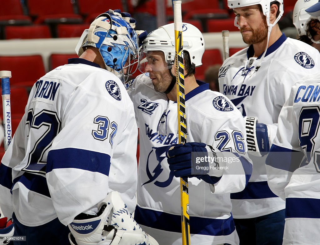 Martin St Louis #26 of the Tampa Bay Lightning is next in line to congratulate Mathieu Garon #32 following their victory over the Carolina Hurricanes following an NHL game on January 22, 2013 at PNC Arena in Raleigh, North Carolina.