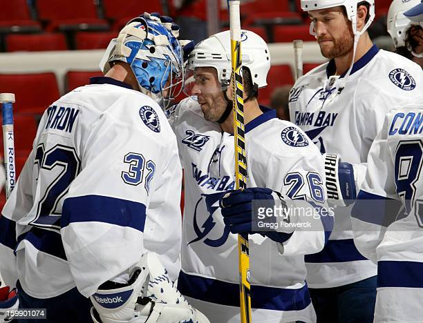 Martin St Louis of the Tampa Bay Lightning is next in line to congratulate Mathieu Garon following their victory over the Carolina Hurricanes...