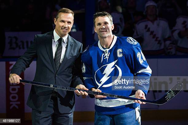 Martin St Louis of the Tampa Bay Lightning is presented with a silver stick commemorating his 1000th NHL game by Tampa Bay Lightning General Manager...