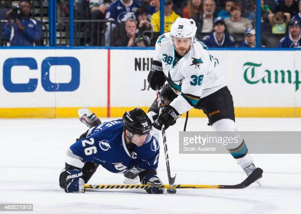 Martin St Louis of the Tampa Bay Lightning is tripped while battling for the puck against Bracken Kearns of the San Jose Sharks during the second...