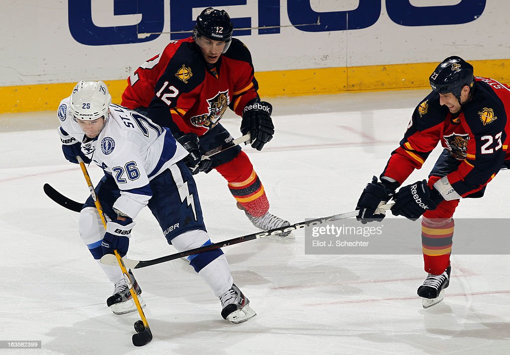 <a gi-track='captionPersonalityLinkClicked' href=/galleries/search?phrase=Martin+St.+Louis&family=editorial&specificpeople=202067 ng-click='$event.stopPropagation()'>Martin St. Louis</a> #26 of the Tampa Bay Lightning tangles with Tyson Strachan #23 aand <a gi-track='captionPersonalityLinkClicked' href=/galleries/search?phrase=Jack+Skille&family=editorial&specificpeople=697014 ng-click='$event.stopPropagation()'>Jack Skille</a> #12 of the Florida Panthers at the BB&T Center on March 12, 2013 in Sunrise, Florida.