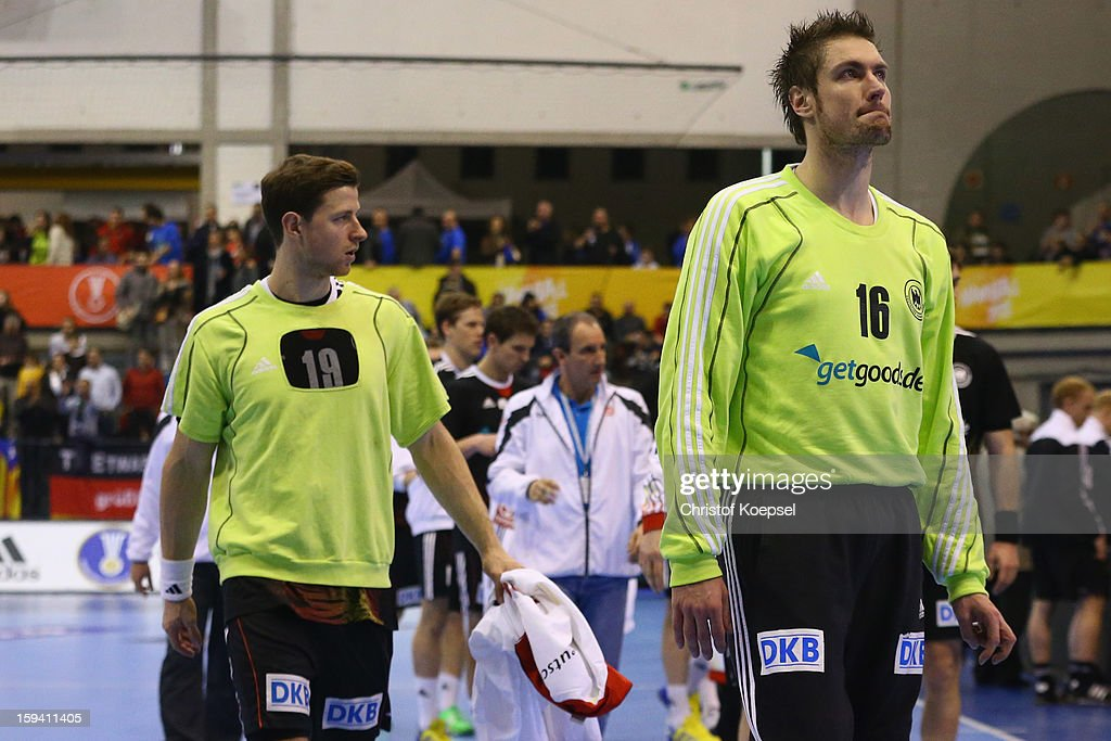Martin Strobel and Carsten Lichtlein of Germany look dejected after the premilary group A match between Tunisia and Germany at Palacio de Deportes de Granollers on January 13, 2013 in Granollers, Spain. The match between Tunisia and Germany ended 25-23.