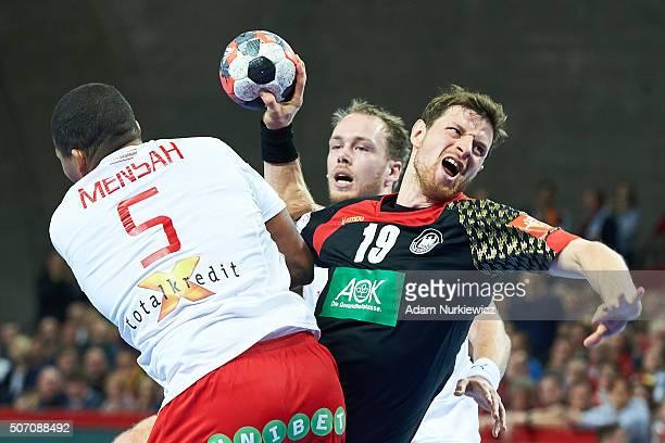 Martin Strobel of Germany throws the ball against Mads Mensah Larsen of Denmark during the Men's EHF Handball European Championship 2016 match...