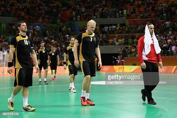 Martin Strobel Patrick Wiencek and Silvio Heinevetter of Germany look dejected after loosing the Men's Handball Semifinal match between France and...