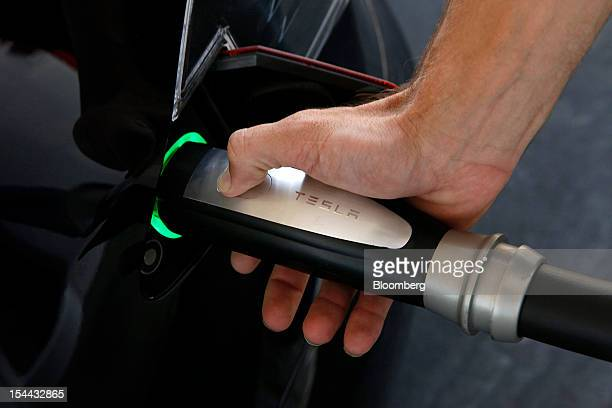 Martin Sukup an electrical engineer for Tesla Motors Inc demonstrates the charging procedure on an S sedan before the grand opening of the Tesla...