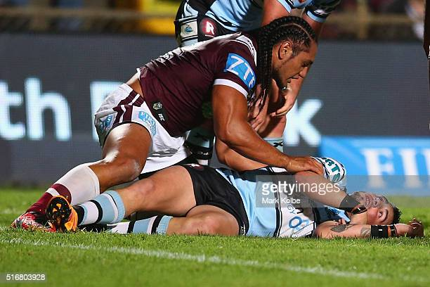 Martin Taupau of the Eagles shows concern for Jack Bird of the Sharks as he lies injured on the ground during the round three NRL match between the...