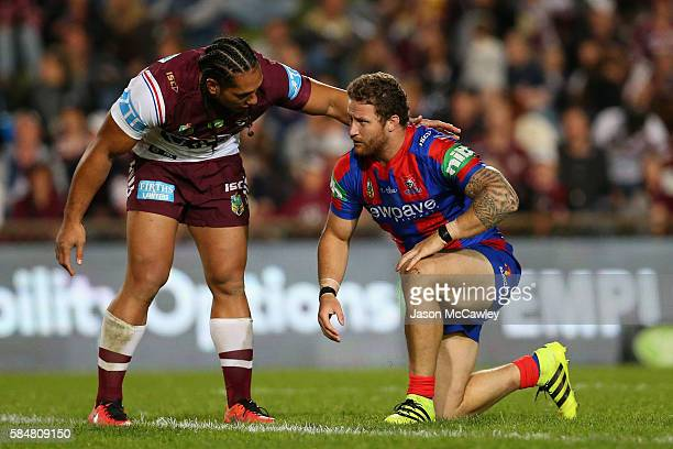 Martin Taupau of the Sea Eagles checks on Korbin Sims of the Knights during the round 21 NRL match between the Manly Sea Eagles and the Newcastle...