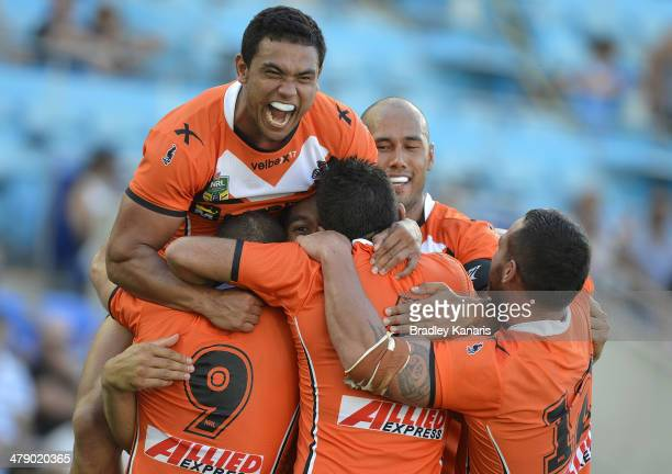 Martin Taupau of the Tigers is swamped by team mates as they celebrate his try during the round two NRL match between the Gold Coast Titans and the...