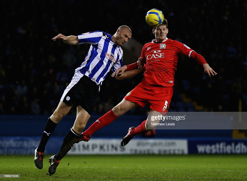 Martin Taylor of Sheffield and Gary MacKenzie of Milton Keynes challenge for the ball during the FA Cup with Budweiser Third Round match between Sheffield Wednesday and Milton Keynes Dons at Hillsborough Stadium on January 5, 2013 in Sheffield, England.