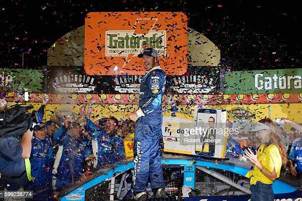 Martin Truex Jr driver of the AutoOwners Insurance Toyota celebrates in Victory Lane after winning the NASCAR Sprint Cup Series Bojangles' Southern...