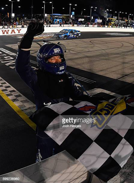 Martin Truex Jr driver of the AutoOwners Insurance Toyota celebrates with the checkered flag after winning the NASCAR Sprint Cup Series Bojangles'...