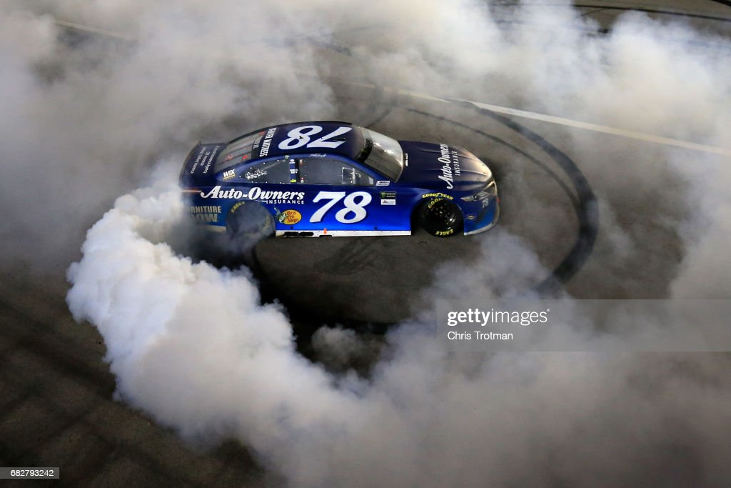 Martin Truex Jr., driver of the #78 Auto-Owners Insurance Toyota, celebrates with a burnout after winning the Monster Energy NASCAR Cup Series Go Bowling 400 at Kansas Speedway on May 13, 2017 in Kansas City, Kansas.
