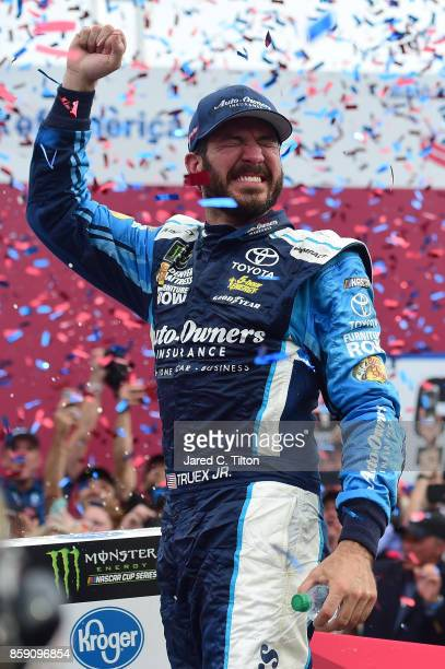 Martin Truex Jr driver of the AutoOwners Insurance Toyota celebrates in Victory Lane after winning the Monster Energy NASCAR Cup Series Bank of...