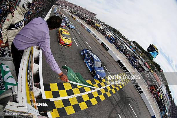 Martin Truex Jr driver of the AutoOwners Insurance Toyota leads the field past the green flag to start during the NASCAR Sprint Cup Series Goody's...