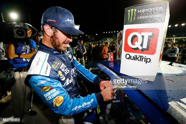 Martin Truex Jr driver of the AutoOwners Insurance Toyota places the winner's decal on his car in Victory Lane during the Monster Energy NASCAR Cup...