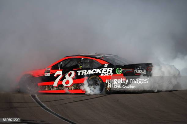 Martin Truex Jr driver of the Bass Pro Shops/TRACKER BOATS Toyota celebrates with a burnout after winning the Monster Energy NASCAR Cup Series Kobalt...