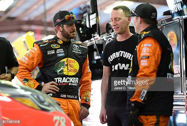 Martin Truex Jr driver of the Bass Pro Shops/TRACKER Boats Toyota and crew chief Cole Pearn are seen in the garage after an ontrack incident during...