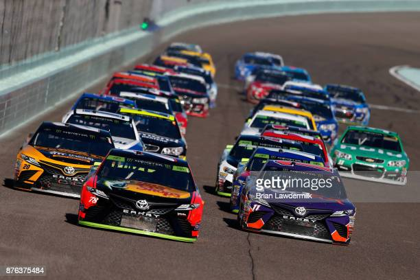 Martin Truex Jr driver of the Bass Pro Shops/Tracker Boats Toyota and Denny Hamlin driver of the FedEx Express Toyota lead a pack of cars during the...