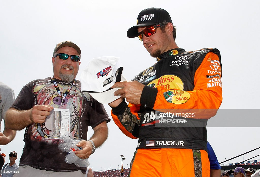 Martin Truex Jr, driver of the #78 Bass Pro Shops/TRACKER Boats Toyota, signs autographs during practice for the NASCAR Sprint Cup Series GEICO 500 at Talladega Superspeedway on April 29, 2016 in Talladega, Alabama.