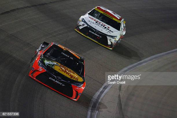Martin Truex Jr driver of the Bass Pro Shops/TRACKER Boats Toyota leads Carl Edwards driver of the Sport Clips Toyota during the NASCAR Sprint Cup...