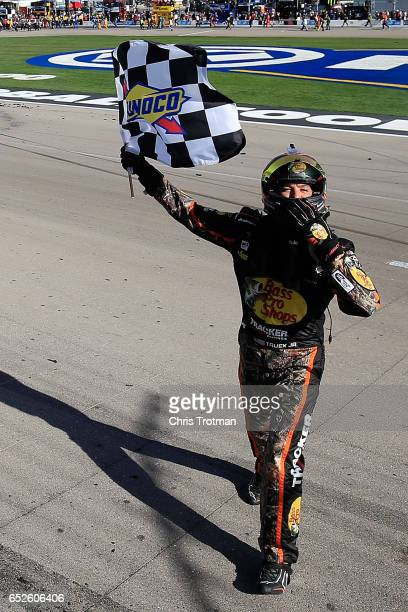 Martin Truex Jr driver of the Bass Pro Shops/TRACKER BOATS Toyota celebrates with the checkered flag after winning the Monster Energy NASCAR Cup...