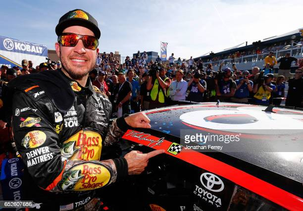Martin Truex Jr driver of the Bass Pro Shops/TRACKER BOATS Toyota poses with the winner's decal on his car in Victory Lane after winning the Monster...