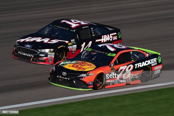 Martin Truex Jr driver of the Bass Pro Shops/Tracker Boats Toyota leads Clint Bowyer driver of the Haas Automation Ford during the Monster Energy...