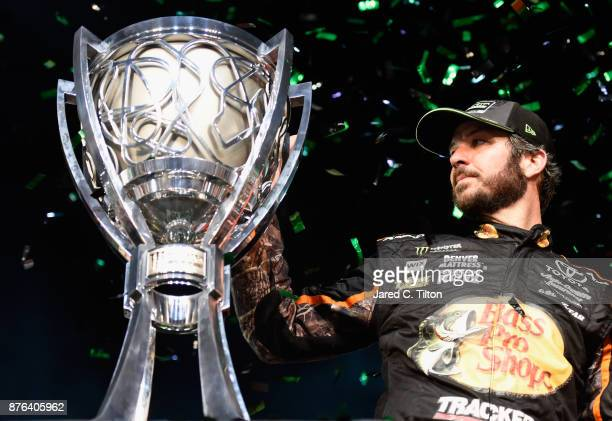 Martin Truex Jr driver of the Bass Pro Shops/Tracker Boats Toyota celebrates with the trophy in Victory Lane after winning the Monster Energy NASCAR...