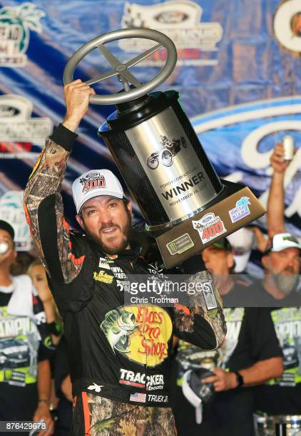 Martin Truex Jr driver of the Bass Pro Shops/Tracker Boats Toyota celebrates with the race trophy after winning the Monster Energy NASCAR Cup Series...