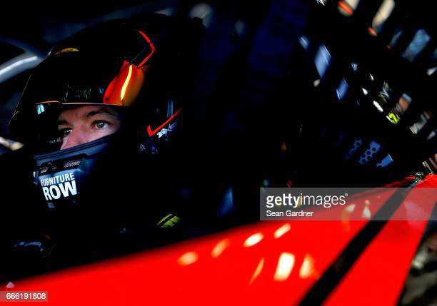 Martin Truex Jr driver of the Bass Pro Shops/TRACKER BOATS Toyota sits in his car during practice for the Monster Energy NASCAR Cup Series O'Reilly...