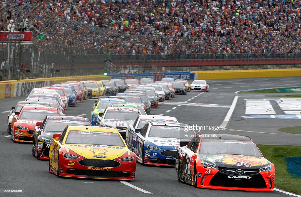<a gi-track='captionPersonalityLinkClicked' href=/galleries/search?phrase=Martin+Truex+Jr.&family=editorial&specificpeople=184514 ng-click='$event.stopPropagation()'>Martin Truex Jr.</a>, driver of the #78 Bass Pro Shops/Tracker Toyota, and <a gi-track='captionPersonalityLinkClicked' href=/galleries/search?phrase=Joey+Logano&family=editorial&specificpeople=4510426 ng-click='$event.stopPropagation()'>Joey Logano</a>, driver of the #22 Shell Pennzoil Ford, lead the field to the green flag to start the NASCAR Sprint Cup Series Coca-Cola 600 at Charlotte Motor Speedway on May 29, 2016 in Charlotte, North Carolina.