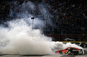 Martin Truex Jr driver of the Bass Pro Shops/Tracker Toyota celebrates with a burnout after winning the NASCAR Sprint Cup Series CocaCola 600 at...