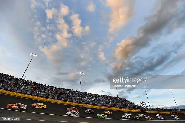 Martin Truex Jr driver of the Bass Pro Shops/Tracker Toyota leads a pack of cars during the NASCAR Sprint Cup Series CocaCola 600 at Charlotte Motor...
