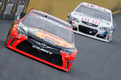 Martin Truex Jr driver of the Bass Pro Shops/Tracker Toyota leads Jimmie Johnson driver of the Lowe's Patriotic Chevrolet during the NASCAR Sprint...