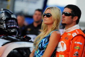 Martin Truex Jr driver of the Furniture Row Chevrolet right and girlfriend Sherry Pollex take part in prerace ceremonies for the NASCAR Sprint Cup...