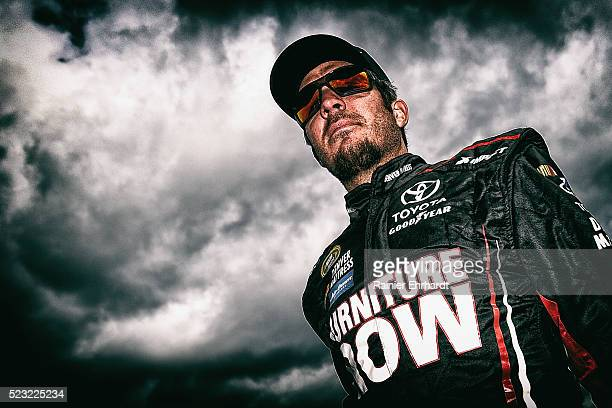 Martin Truex Jr driver of the Furniture Row Toyota walks in the garage area during practice for the NASCAR Sprint Cup Series TOYOTA OWNERS 400 at...